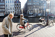 In Amsterdam rijdt een touriste op een huurfiets over de Kloveniersburgwal.<br /> <br /> In Amsterdam a tourist is riding on a rental bike at the Kloveniersburgwal.