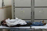 Sco0033837 .  Daily Telegraph..The corpse of a man lies on a bed next to the refrigeration units at Tripoli Central Hospital's overflowing morgue...Tripoli 25 August 2011. ............Not Getty.Not Reuters.Not AP.Not Reuters.Not PA