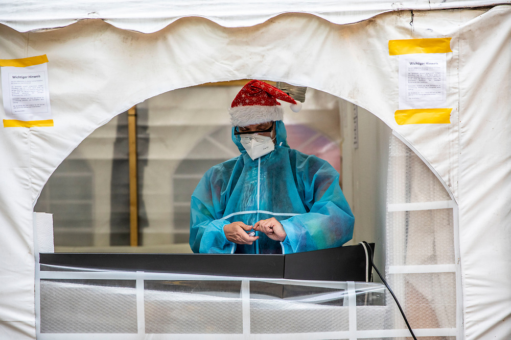 Medical personnel staff member wears a Santa hat at a covid-19 test station outside the Kitkat night club in Berlin, Germany, December 13, 2020. Berlin's world famous KitKatClub has initiated a fast covid-19 tests operation in its premises People are able to set an online appointment and arrive to have a covid antigen rapid test swab test in what was reported by local media outlet as the lowest price in the German capital. The club itself is closed since early 2020 due to the health restrictions imposed on cultural venues in Germany.