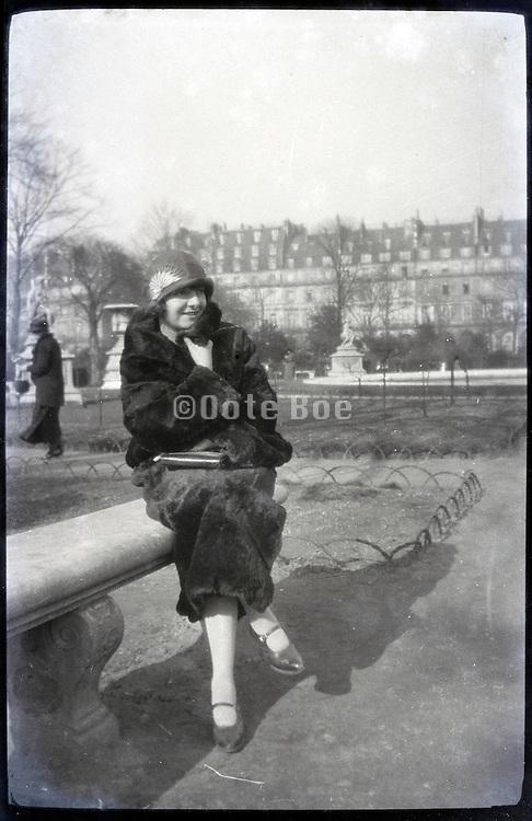 female person wearing fur coat in park Paris 1900s