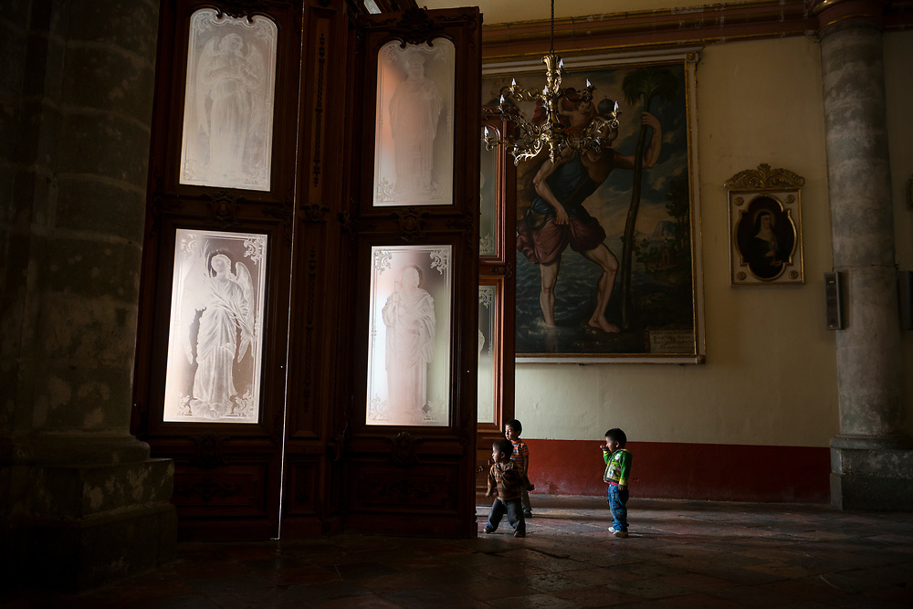 Three young boys play inside the Cathedral of Our Lady of the Assumption in the Mexican city of Oaxaca.