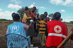 Refugee status cards are handed out by UNHCR and Uganda Red Cross. More than 300,000 South Sudanese refugees have fled from the country's civil war into Uganda since fighting broke out in July. They mostly travel by foot for days through the bush as roads have been blocked or are too dangerous to cross. The massive influx of refugees has caused a strain in humanitarian aid due to large numbers and lack of funding. BidiBidi settlement is now the third largest in the world and holds more than 210,000 people since its opening in September.