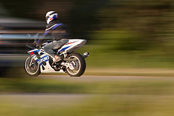 A man rides his motorcycle.  Through a creative technique, I have made the image look as though the motorcycle is in reverse.