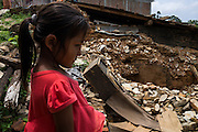Monika Baniya (7) looks at the rubble of what used to be her family home in Chautara, Sindhupalchowk, Nepal on 29 June 2015. Her younger sister Aastha was buried under the rubble together with her mother but Aastha survived while her mother died on the spot. As their father Ratna Baniya (28) cannot care for the children on his own, SOS Childrens Villages has since been supporting the grandmother with financial and social support so that she can manage to raise the children comfortably and ensure that they will all be schooled. Photo by Suzanne Lee for SOS Children's Villages