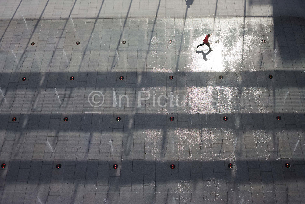"""Seen from an aerial view far above the ground level, is a young boy who leaps across a fountain water feature landscape outside Heathrow Airport's Terminal 5 building <br /> created by the Richard Rogers Partnership (now Rogers Stirk Harbour and Partners). The highlight of a high sun glints off the wet pavement as 55 Choreoswitch waterswitches made by Ocmis are linked to 11 pumps located in a purpose built basement plant room beneath the Plaza. The switches are linked to a unit that also controls the 110 colour changing LED lights integrated into the nozzle housings. Displays can be fast and energetic with dramatic colours or subdued and gentle. From writer Alain de Botton's book project """"A Week at the Airport: A Heathrow Diary"""" (2009)."""
