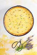Top view of lemon and lavender cake on yellow background