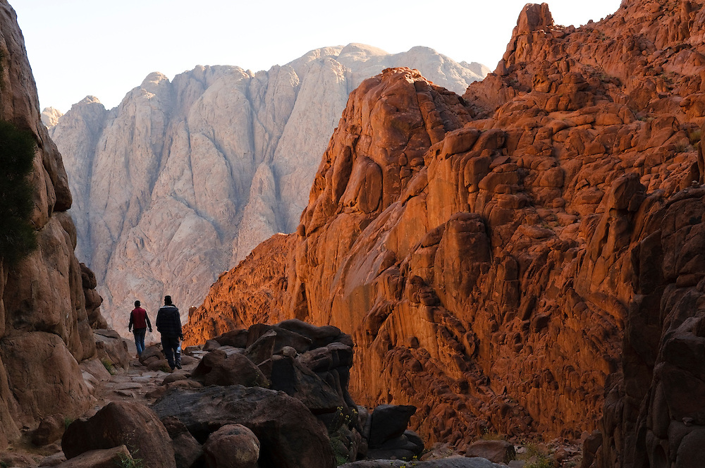 Three hikers descending Mount Sinai in early morning. There are two primary routes up and down the mountain. These hikers are descending via the Steps of Penitence route. The mountain, associated with Moses and the Ten Commandments, is a popular travel destination for religious and secular visitors alike.<br /> (Mount Sinai, Egypt - May 2010)