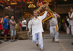 © Licensed to London News Pictures. 21/10/2015 Ipoh, Malaysia. Devotees carry a Emperor God out of the temple in preparation to walk over a bed of hot embers to purify their soul during a fire-walking ceremony on the last day of the Nine Emperor Gods Festival at Tow Boh Keong temple in Ipoh, Malaysia, Wednesday, Oct. 21, 2015. The festival is a nine-day Taoist celebration to mark the birth of the Nine Emperor Gods from the first day to the ninth day of the ninth moon in Chinese Lunar Calender. The origin of the Nine Emperor Gods (stars of the Northern constellation) can be traced back to the Taoist worship of the Northern constellation during Qin and Han Dynasty and absorb this practice of worshipping the stars and began to deitify them as Gods. Photo credit : Sang Tan/LNP