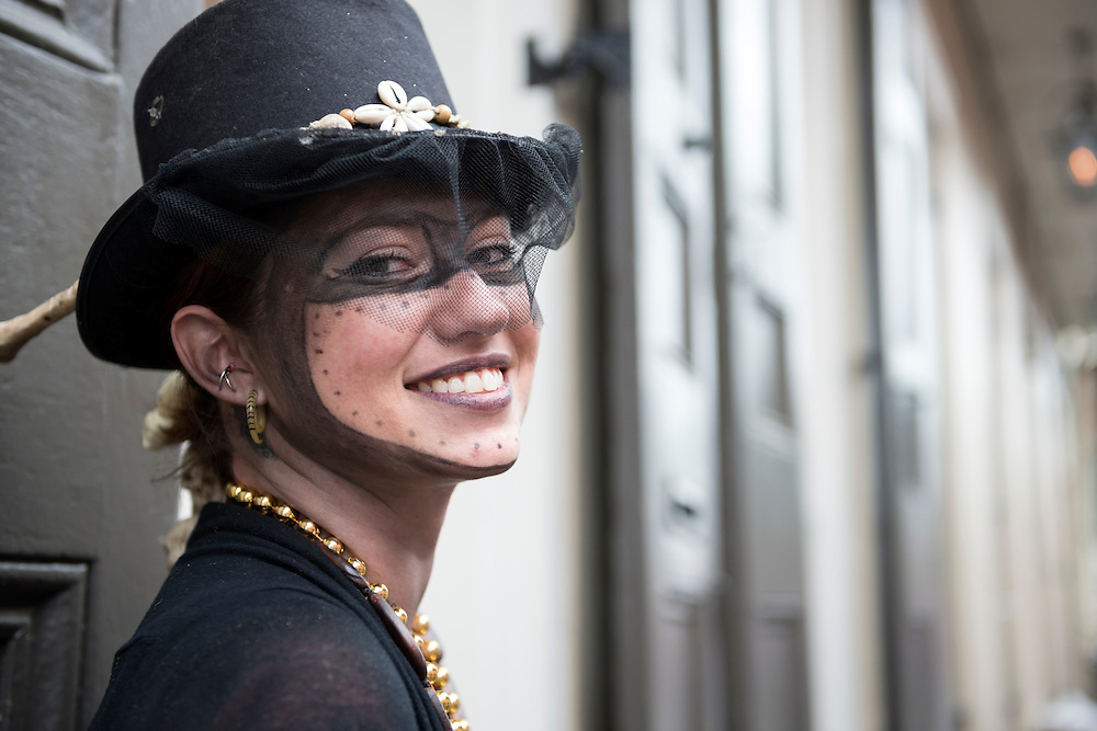 A young woman sits in the French Quarter of New Orleans, dressed up for Mardi Gras festivities on Fat Tuesday.