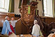 Sixtuskerk Sexbierum tijdens open dag tijdens Tsjerkepaad. Organist Gerrit de Vries vertelt enkele enthousiaste bezoekers over het fraaie houtsnijwerk van de kansel.