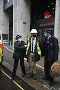Activists scale the entrance to the Department For Work and Pensions, blocking it with people who were locked-on, on the 8th of February 2021, London, United Kingdom. The activists demanded to speak to the Health and Safety executive from the DWP to raise their concerns about the treatment of the activists in Euston Gardens who are currently underground in a tunnel in Euston Gardens, outside Euston Station to stop the building works related to the high speed train project HS2. The activists are concerned about the way the bailiffs and the National Eviction. The activists stopped their protest not to hold up ambulances which were called in by police for their safety. One activist was detained but soon after released and no arrest were made. All were given and accepted fines for breaching Covid-19 rules. The peaceful direct action included dirt brought from the tunnel in Euston Garden, people locked on, a pretend security guard and pretend Health and Safety Executive.