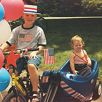 When was this photo taken?<br /> <br /> Fourth of July, 2004 or 2005<br /> <br /> Where was this photo taken?<br /> <br /> John Strange Elementary School, Indianapolis<br /> <br /> Who took this photo?<br /> <br /> John Thomas<br /> <br /> What are we looking at here?<br /> <br /> Our neighborhood used to have a kids' parade every Fourth of July. The kids would decorate their bikes and wagons, the Fire Department would bring a fire truck to lead the parade, and we would walk through the parking lot at John Strange School, just a few blocks from our house. Our kids were about 2 and 7 at the time ... now they're 17 and 22.<br /> <br /> How does this old photo make you feel?<br /> <br /> First, delighted to see my kids as little ones! And happy to see old friends and a great neighborhood tradition. But then a little sad: As the families in this group got older, no others picked up responsibility for the tradition, so the annual parade is no more. And the school, which both kids attended, is closing.<br /> <br /> Is this what you expected to see?<br /> <br /> I had no idea what to expect ... I had feared the roll might be boring, mundane work photos or something ... so my wife and I were pleasantly surprised!