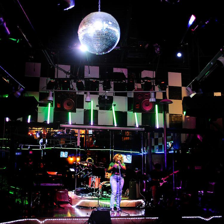 Nekita Waller sings under a large disco ball at Vibz nightclub in Hartford