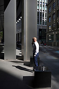 A financial services worker takes a cigarette break in reflected light from a nearby skyscraper in the City of London, the capital's financial district aka the Square Mile, on 17th May 2018, in London, UK.