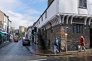 With the medieval castle dominating the town, a couple walk past the 14th century Merchant's House on Conwy high street, on 4th October 2021, in Conwy, Gwynedd, Wales. The walls were constructed between 1283 and 1287 after the foundation of Conwy by Edward I, and were designed to form an integrated system of defence alongside Conwy Castle. The walls are 1.3 km (0.81 mi) long and include 21 towers and three gatehouses. Conwy is a walled market town and community on the north coast of Wales.