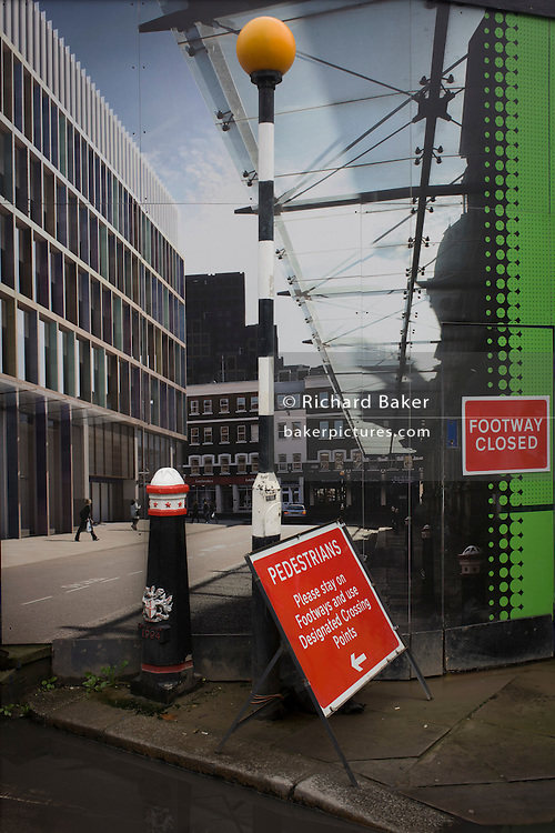 Crossrail construction hoarding of Smithfield scene placed alongside real street signs and bollard