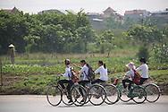 Group of pupils in uniform ride back home from school. Vietnam, Southeast Asia