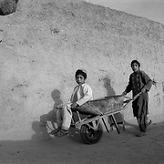Jun 14, 2009 - Kandahar Province, Afghanistan - Afghan children seen by their homes as a patrol of Canadian troops passes by in the Pashmul area of Zhari District west of Kandahar City, Afghanistan.<br /> (Credit Image: © Louie Palu/ZUMA Press)