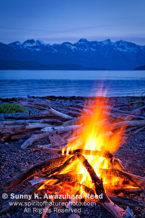 Campfire at a remote coast in Glacier Bay National Park & Preserve, Southeast Alaska at dusk.  Snow capped mountains in the background.