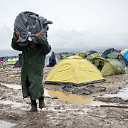 A man walks with all the possessions wrapped in UNHCR blanket in a flooded muddy field near the transit camp of Idomeni, Greece. <br /> <br /> Thousands of refugees are stranded in Idomeni unable to cross the border. The facilities are stretched to the limit and the conditions are appalling.