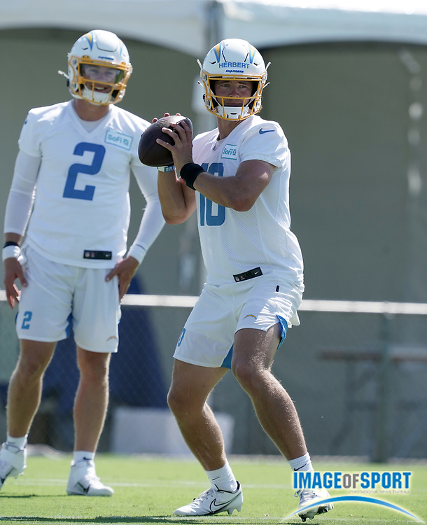 Aug 14, 2020; Costa Mesa, California, USA; Los Angeles Chargers quarterback Justin Herbert (10) throws the ball as quarterback Easton Stick (2) watches during training camp at the Jack Hammett Sports Complex.