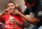 """Denim Manygoats, 6, (left), has an image of the UA mascot, a """"Wildcat,"""" painted on his face by UA student, Asha Greyeyes, of Monument Valley before the football game during the NASA Wildcat Family Pride Weekend at the University of Arizona, Tucson, Arizona, USA."""