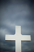 Low angle view of white cross at cemetery with dramatic sky in background