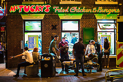 © Licensed to London News Pictures . 11/09/2016 . Manchester , UK . A woman is carried in to an ambulance on a trolley outside McTucky's Fried Chicken and Burgers , in the Gay Village . Revellers out in Manchester City Centre . Photo credit : Joel Goodman/LNP