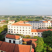 A high resolution panorama of the skyline of Hue in east-central Vietnam, with modern buildings in the foreground and the Perfume River in the background.