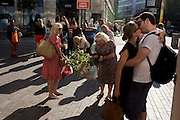 Visitors to the RHS Chelsea Flower Show make their way home through Sloane Square after the last day's plant sell-off.