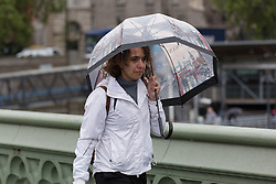 © Licensed to London News Pictures. 14/05/2015. London, UK. A woman with an umbrella during heavy rain and wet and windy weather in Westminster, central London today. Photo credit : Vickie Flores/LNP