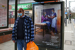 © Licensed to London News Pictures. 20/03/2021. London, UK. A commuter wearing a face covering at a bus stop standing next to the 'It's about our healthcare' the Office for National Statistics (ONS) Census Day 2021 poster in north London. The Census Day is on 21 March 2021. Every household located in England, Wales and Northern Ireland is legally obligated to fill out the survey or could be fined up to £1,000. The ONS is planning on publishing the initial findings from the Census in March 2022, followed by the full results covering all Census data in March 2023. Photo credit: Dinendra Haria/LNP