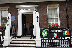 London, UK. 10 July, 2019. A banner brought by Members of the Senegalese community in the UK to a protest outside Chatham House during an interview by Evan Davis of BP Group Chief Executive Bob Dudley to discuss balancing increasing energy needs  with climate change considerations. The protest followed a BBC Panorama exposé on a $10bn petrol and gas corruption scandal in Senegal for which they hold BP accountable, as well as the awarding of an oil exploitation contract through Timis Corporation.