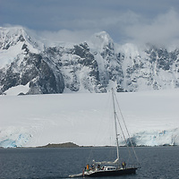 A sailboat motors in the Neumayer Channel,  below the Seven Sisters of Fief in the Fief Mountains on Wienke Island, Antarctica.