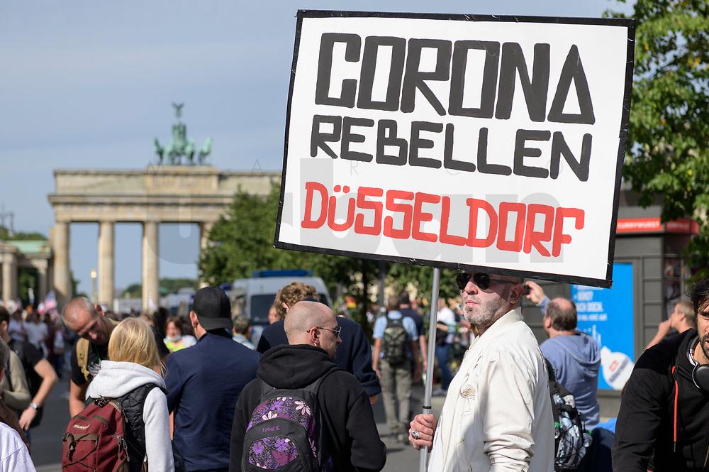 """29 AUG 2020, BERLIN/GERMANY:<br /> Demonstrant mit Plakat """"Corona Rebellen Düsseldorf"""" vor dem Brandenburger Tor, Demonstration gegen die Einschraenkungen in der Corona-Pandemie durch die Initiative """"Querdenken 711"""" aus Stuttgart unter dem Motto """"invites Europa - Fest für Freiheit und Frieden"""", Unter den Linden<br /> IMAGE: 20200829-01-006<br /> KEYWORDS: Demo, Protest, Demosntranten, Protester, COVID-19, Corona-Demo"""
