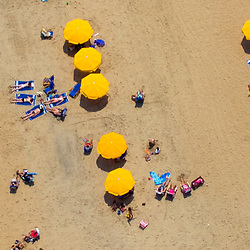Aerial view of sunbathers and Yellow umbrellas on a Delaware Beach