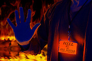 A man wearing a glowing All Access pass holds up his hand as if to block access to hell. Blacklight photography.