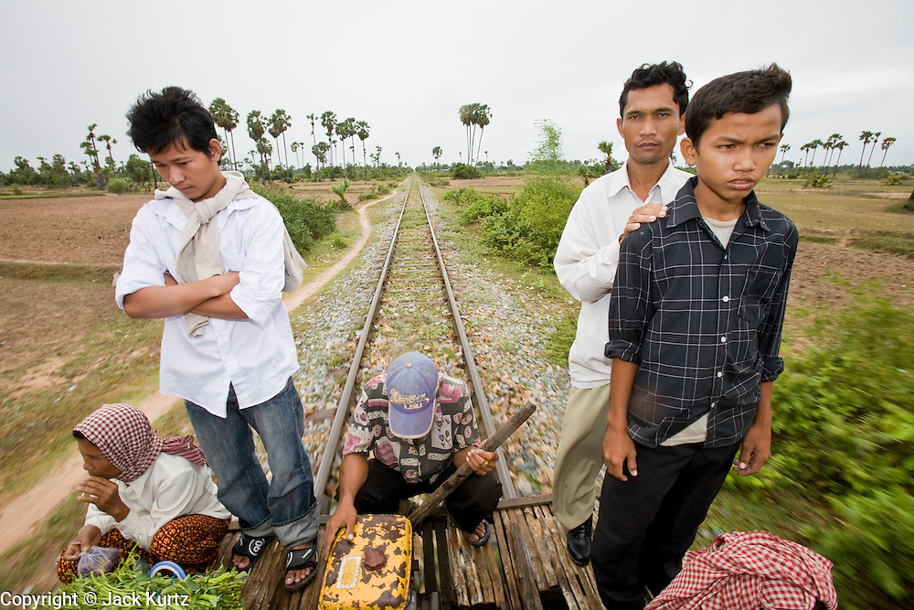 """01 JULY 2006 - PHNOM PENH, CAMBODIA: Passengers ride a bamboo train while the train driver (center) operates it in rural Cambodia. The """"bamboo trains"""" run along the government tracks in rural Cambodia. Bamboo mats are fitted over wheels which ride on the rails. The contraption is powered by a either a motorcycle or lawn mower engine. The Cambodian government would like to get rid of the bamboo trains, but with only passenger train in the country, that runs only one day a week, the bamboo trains meet a need the government trains do not. While much of Cambodia's infrastructure has been rebuilt since the wars which tore the country apart in the late 1980s, the train system is still in disrepair. There is now only one passenger train in the country. It runs from Phnom Penh to the provincial capitol Battambang and it runs only one day a week. It takes 12 hours to complete the 190 mile journey.  Photo by Jack Kurtz / ZUMA Press"""