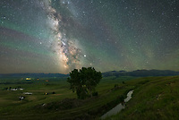 It's a view I came across in early spring: a lone tree on top of a hill overlooking ranches, ponds, a canal, and the Bighorn Mountains. The milky way was the perfect backdrop when I returned to shoot it on a warm night in July. The green stripes in the sky are from a phenomenon called airglow. During the day sunlight ionizes oxygen atoms in the upper atmosphere, and their recombination at night emits a small amount of light. This chemical reaction occurs about 100km up at the same height as the aurora, which is caused by a different process. Ripples in the airglow come from gravity waves, which may originate from the jet stream or a particularly powerful thunderstorm complex. I often find airglow in my pictures anytime I'm shooting under a dark sky. But this night was the strongest I've ever seen it. The wave pattern was very apparent, although the color was undetectable to my eyes.