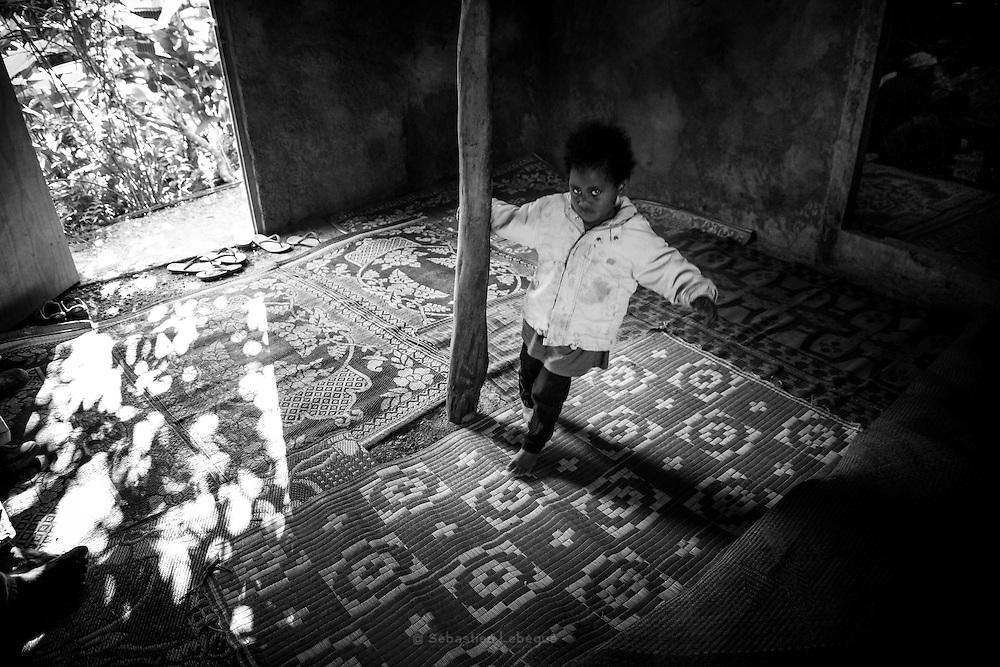 NOUVELLE CALEDONIE, HIENGHENE, Aire coutumière de Hoot Ma Waap, Tendo - Aout 2013 - une fille tourne autour du poteau central. Dans l'autre salle, les pleurs des femmes - Ceremonie du deuil dans la coutume Kanak. Les femmes s'asseoient proche du lit et accompagne la mère dans les larmes et les pleurs. Ensuite l'homme prend la parole debout et remet au mort une coutume composé d'un Manu et d'un billet. [EN] Wailing - Bereavement in Kanak Custom - New Caledonia - August 2013