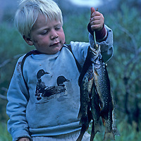 A youngster admires trout he caught in a Sierra Nevada stream.