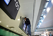 A worker installs TV screens at the nearly completed new terminal of the Hongqiao Airport in Shanghai, China on 21 January 2010.  The new terminal is a part of the larger Hongqiao Transportation Hub that will combine air, high-speed rail, and maglev links.