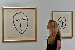 """© Licensed to London News Pictures. 01/08/2017. London, UK. A staff member views (L to R) """"Large Face (Mask)"""", 1952, and """"Large Mask"""", 1948.  Preview of """"Matisse in the Studio"""", at the Royal Academy of Arts, Piccadilly, the first exhibition to consider how the personal collection of treasured objects of Henri Matisse were both subject matter and inspiration for his work.  Around 35 objects are displayed alongside 65 of Matisse's paintings, sculptures, drawings, prints and cut-outs.  The exhibition runs 5 August to 12 November 2017.  Photo credit : Stephen Chung/LNP"""