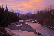 Braided river banks of Glacier Creek  in Girdwood, Alaska during winter. Colorful alpenglow lights up the snowy slopes of Chugach Mountains.