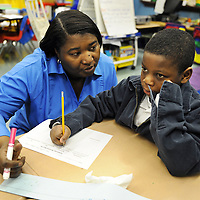 Ms. Mobley helps JaJuan, deep in thought, spell out a word for his worksheet.