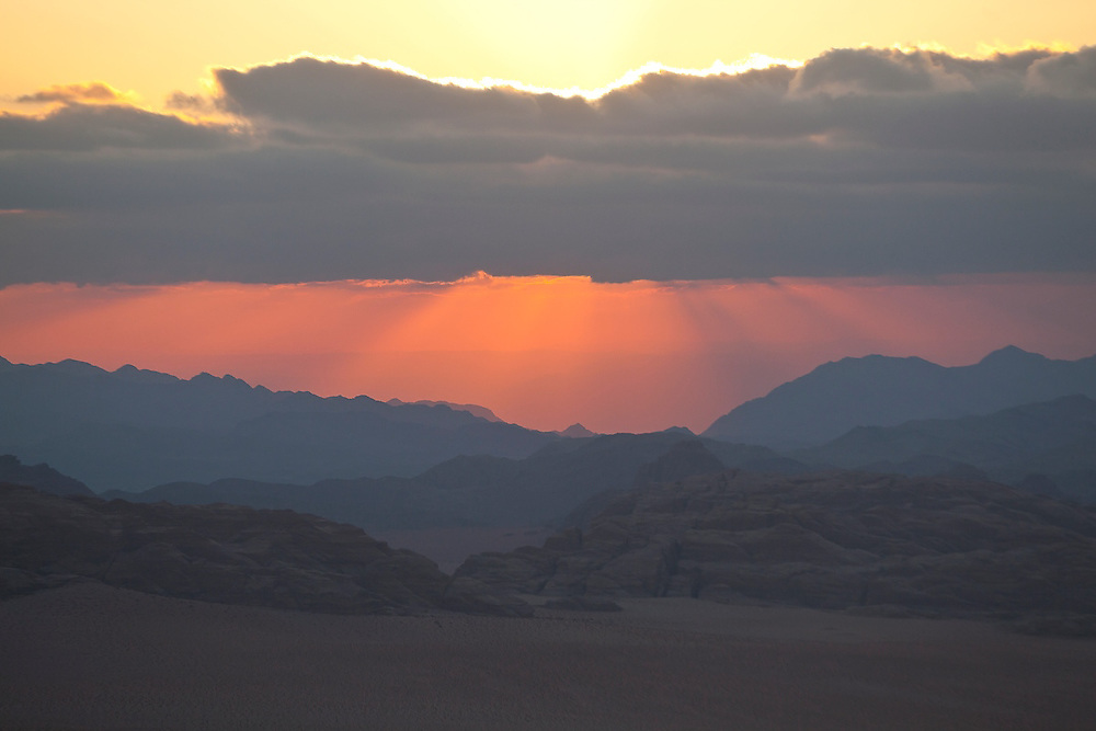 Sunset over the distant mountains of Saudi Arabia, seen from southern Wadi Rum, Jordan.