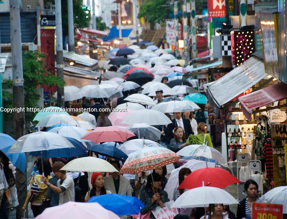 Many umbrellas in the rain in busy trendy Takeshita Street in Harajuku Tokyo