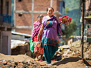 03 AUGUST 2015 - SANKHU, NEPAL:  A woman walks down a street still strewn with debris from the earthquake in Sankhu, a community about 90 minutes from central Kathmandu. The Nepal Earthquake on April 25, 2015, (also known as the Gorkha earthquake) killed more than 9,000 people and injured more than 23,000. It had a magnitude of 7.8. The epicenter was east of the district of Lamjung, and its hypocenter was at a depth of approximately 15 km (9.3 mi). It was the worst natural disaster to strike Nepal since the 1934 Nepal–Bihar earthquake. The earthquake triggered an avalanche on Mount Everest, killing at least 19. The earthquake also set off an avalanche in the Langtang valley, where 250 people were reported missing. Hundreds of thousands of people were made homeless with entire villages flattened across many districts of the country. Centuries-old buildings were destroyed at UNESCO World Heritage sites in the Kathmandu Valley, including some at the Kathmandu Durbar Square, the Patan Durbar Squar, the Bhaktapur Durbar Square, the Changu Narayan Temple and the Swayambhunath Stupa. Geophysicists and other experts had warned for decades that Nepal was vulnerable to a deadly earthquake, particularly because of its geology, urbanization, and architecture.    PHOTO BY JACK KURTZ