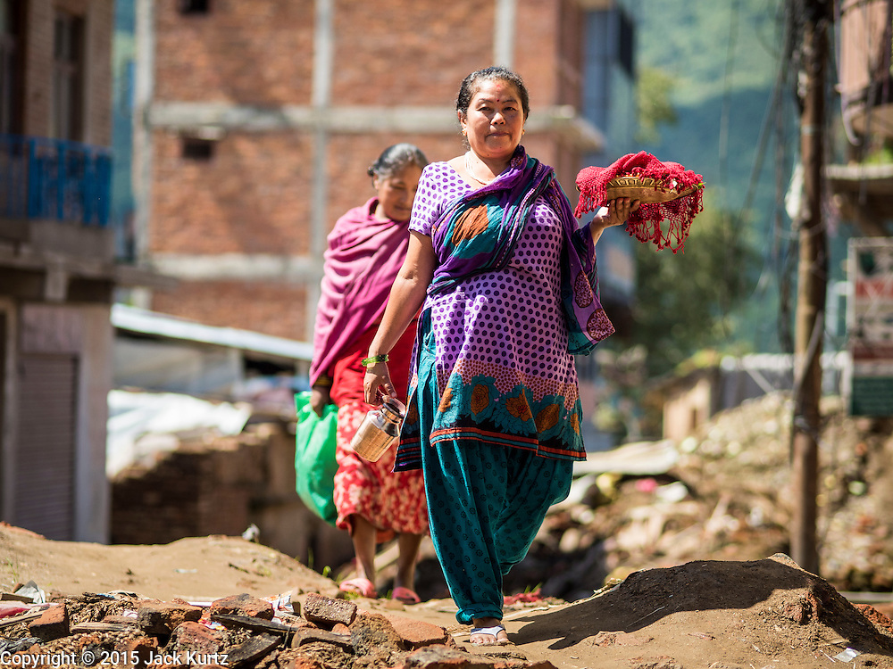 03 AUGUST 2015 - SANKHU, NEPAL:  A woman walks down a street still strewn with debris from the earthquake in Sankhu, a community about 90 minutes from central Kathmandu. The Nepal Earthquake on April 25, 2015, (also known as the Gorkha earthquake) killed more than 9,000 people and injured more than 23,000. It had a magnitude of 7.8. The epicenter was east of the district of Lamjung, and its hypocenter was at a depth of approximately 15km (9.3mi). It was the worst natural disaster to strike Nepal since the 1934 Nepal–Bihar earthquake. The earthquake triggered an avalanche on Mount Everest, killing at least 19. The earthquake also set off an avalanche in the Langtang valley, where 250 people were reported missing. Hundreds of thousands of people were made homeless with entire villages flattened across many districts of the country. Centuries-old buildings were destroyed at UNESCO World Heritage sites in the Kathmandu Valley, including some at the Kathmandu Durbar Square, the Patan Durbar Squar, the Bhaktapur Durbar Square, the Changu Narayan Temple and the Swayambhunath Stupa. Geophysicists and other experts had warned for decades that Nepal was vulnerable to a deadly earthquake, particularly because of its geology, urbanization, and architecture.    PHOTO BY JACK KURTZ