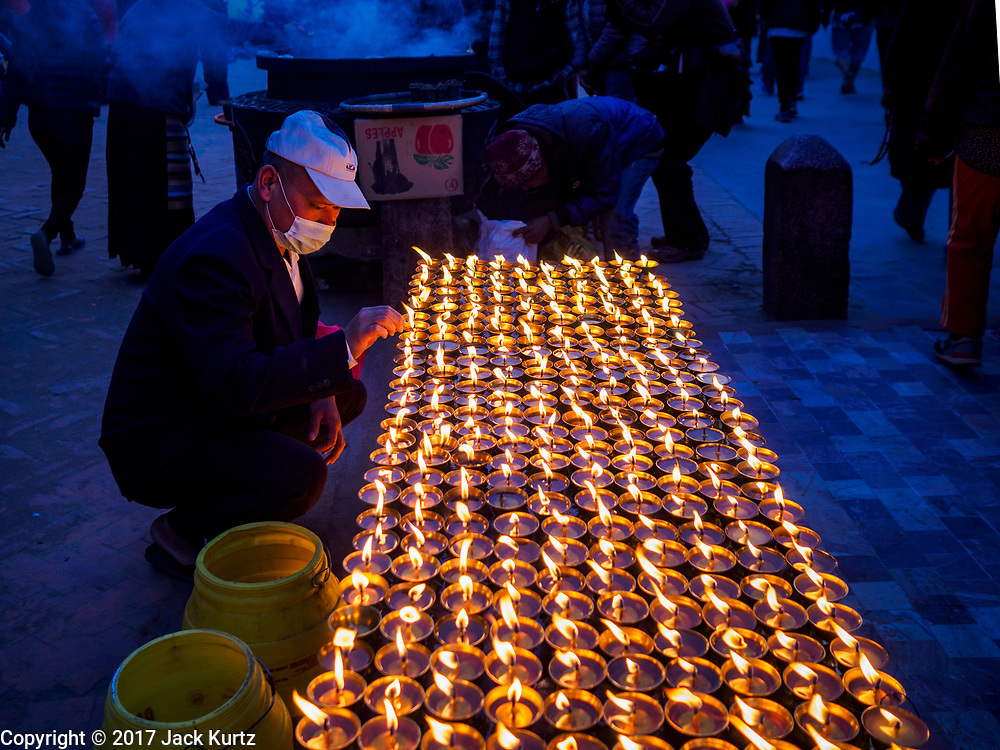 16 MARCH 2017 - KATHMANDU, NEPAL:  A man lights butter lamps at a Tibetan Buddhist monastery next to Boudhanath Stupa in Kathmandu. Boudhanath Stupa is the holiest site in Nepali Buddhism. It is also the center of the Tibetan exile community in Kathmandu. The Stupa was badly damaged in the 2015 earthquake but was one of the first buildings renovated.      PHOTO BY JACK KURTZ